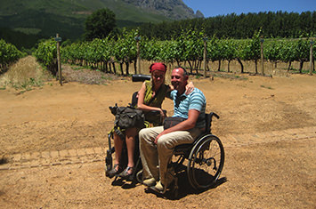 A lady and a man sitting in a wheelchair smiling on a beautiful sunny day with green little trees in the background