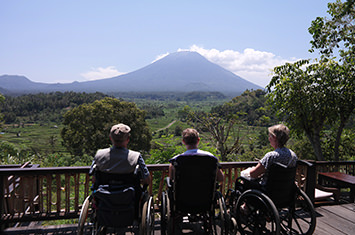 3 people in a wheelchair viewing a mountain