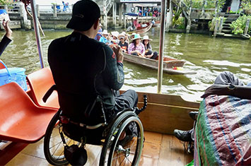 A guy in a wheelchair on a boat in Thailand