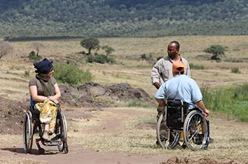 2 wheelchair users with guide in Tanzania