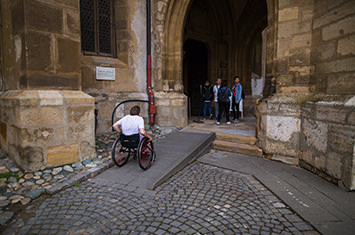 Man in a wheelchair riding up a ramp into a historical building