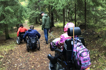 3 people in wheelchairs in the nature and a guide