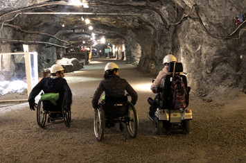 3 people in a wheelchair in a mine