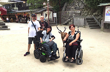2 people in a wheelchair and a deer behind them and two standing men next to the ladies